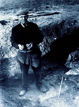 black and white photo of Basil Brown standing in trench