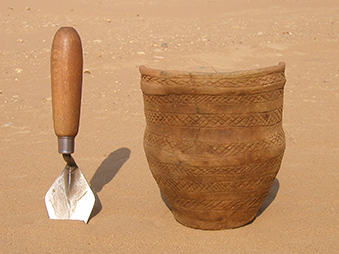 a neolithic pot next to a trowel