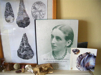 a collection of objects on a table, a framed photo of hand axes and a book about Layard