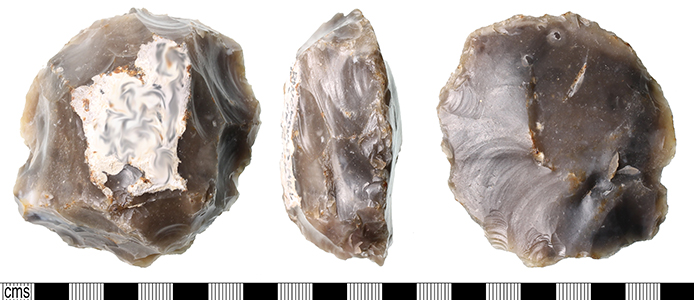 a heavily flaked flint levallois core, roughly circular with flakes taken from edges.