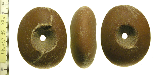 an ovoid pebble macehead with perforation through the centre, image shows 3 sides