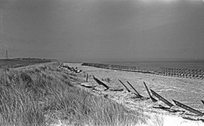 wartime photo of scaffolding and 'Dragon's Teeth' on beach