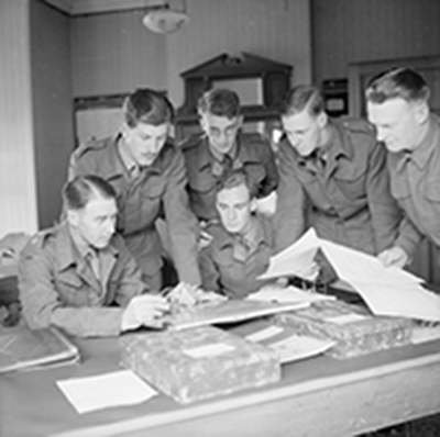 wartime photo of six officers gathered around a desk reviewing paperwork